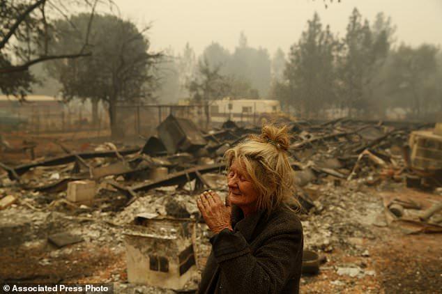 """Cathy Fallon reagiert, als sie in der Nähe der verbrannten Überreste ihres Hauses steht, Freitag, 9. November 2018, in Paradise, Kalifornien. """"Ich werde verdammt sein, wenn ich diese Pferde im Feuer brennen lassen werde"""", sagte Fallon , die sich auf ihrem Besitz aufhielt, um ihre 14 Pferde zu schützen, die alle überlebten. (AP Foto / John Locher)"""