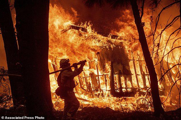 Le pompier Jose Corona aspire de l'eau alors que les flammes du camp brûlent, un incendie détruit une maison à Magalia, en Californie, le vendredi 9 novembre 2018. (Photo AP / Noah Berger)