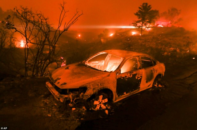 A burned vehicle is seen on the Pacific Coast Highway in Malibu, California on Friday as the Woolsey Fire races toward the sea