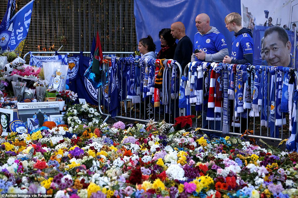 The devotees shared the silence as they gazed at the many colors of the floral tribute outside the King Power
