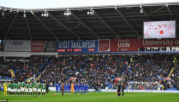Both groups of players line up around the central circle during one minute of silence before kick-off on Saturday afternoon