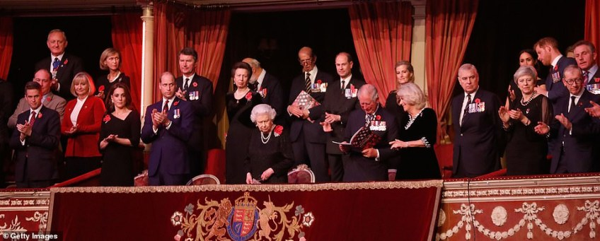 The royal family stand in applause as the show begins. Charles reads the event programme, which is produced by the event organisers, the Royal British Legion