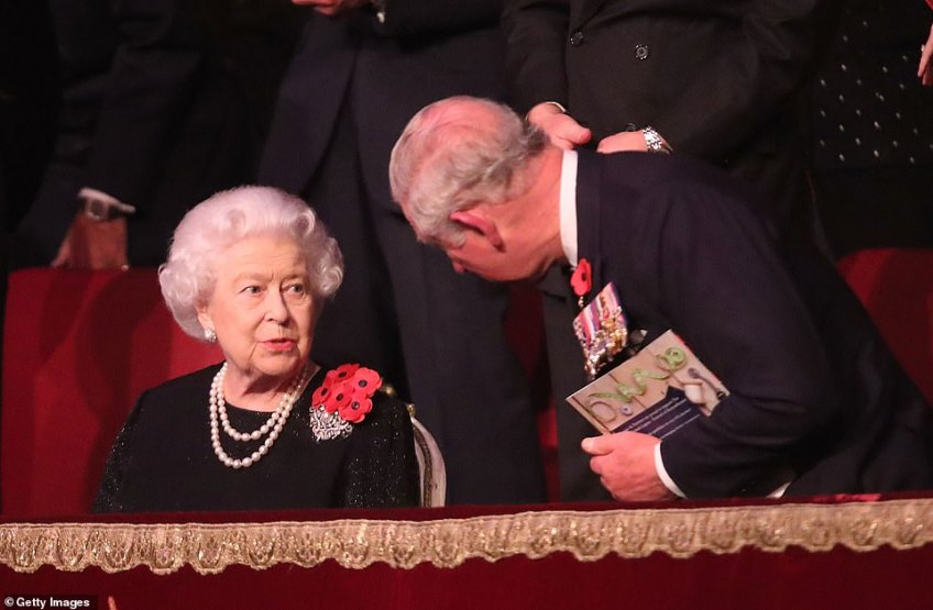 Charles, Prince of Wales, clutching a programme from tonight leans down to listen to Queen Elizabeth II