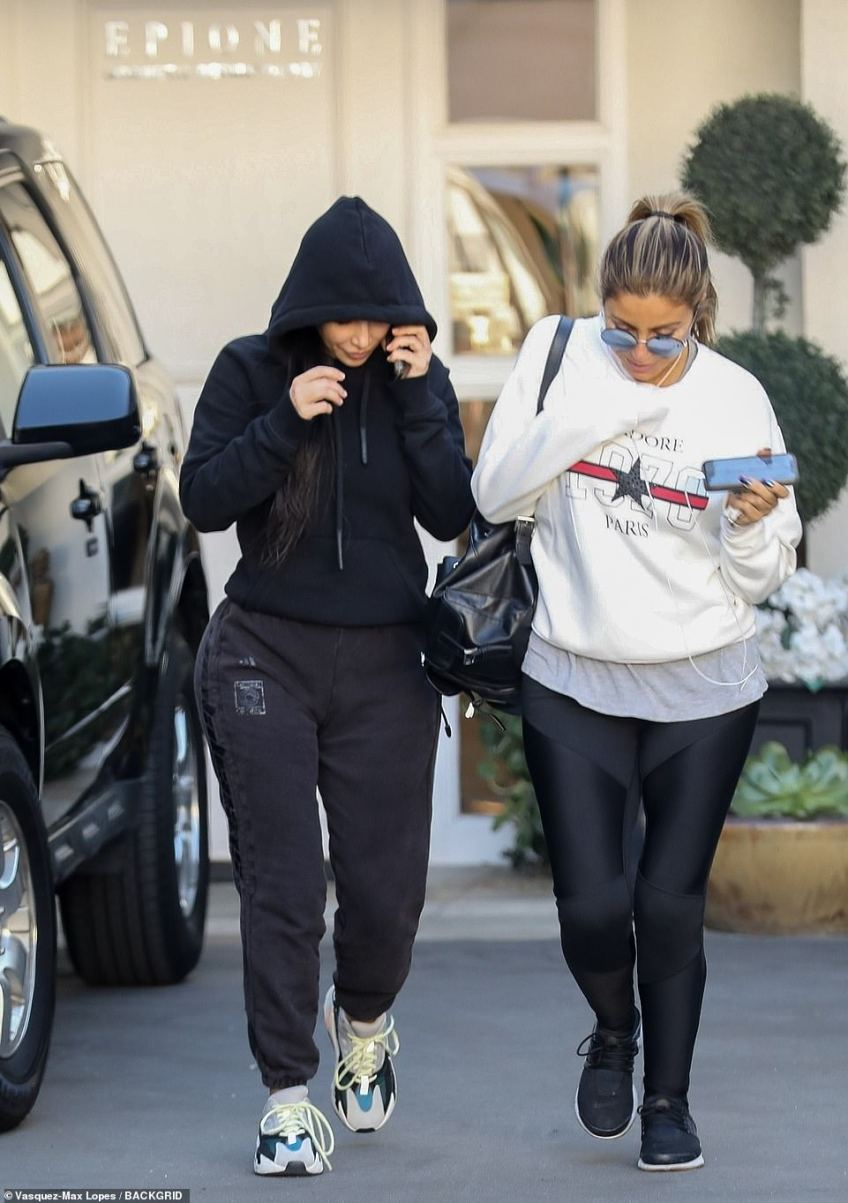 Interesting: The reality star tried to keep a low radar in a black hoodie and matching sweats while leaving Epione on Friday; pictured with Larsa Pippen