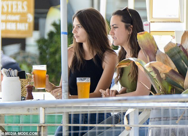 Refreshments!Cutting a casual figure in a black midriff and light wash jeans, the 27-year-old model and actress appeared relaxed as she enjoyed her large glass of ale at the trendy beachside bar