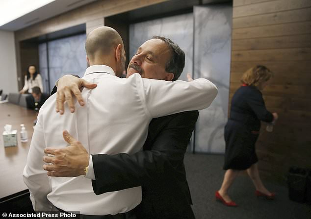 Dr Assaad Sayah, chief medical officer of Cambridge Health Alliance, right, embraces Pete DeMarco Nov. 13, 2018 after a meeting where he and other executives answered questions on the death of DeMarco's wife, Laura Levis, in Boston (Boston Globe / AP)