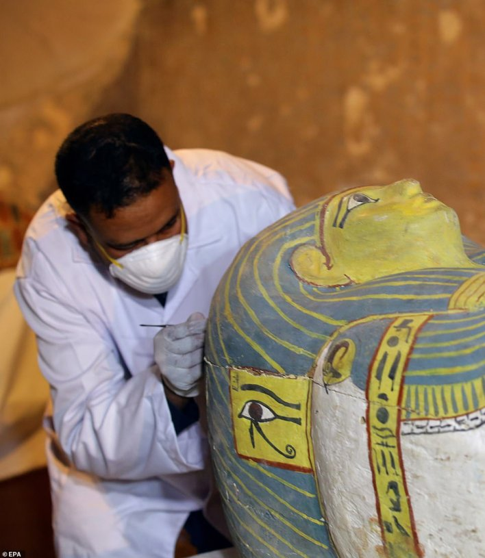 Egyptian archaeologists move the cover of an intact sarcophagus, inside Tomb TT33 in Luxor, containing the 'perfectly intact' 3,000-year-old woman