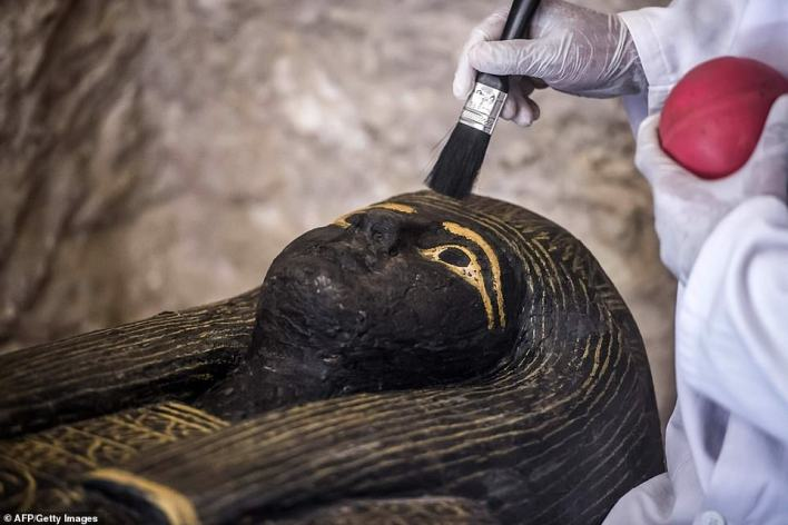An Egyptian archaeologist brushes the top of a carved black wooden sarcophagus inlaid with gilded sheets on November 24, 2018