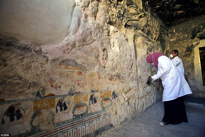 Egyptian archaeologists work on restoring a wall with painted murals inside the newly discovered tomb at al-Assassif Necropolis
