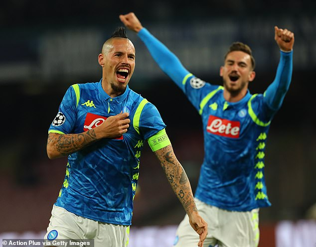 The Napoli playmaker points to the badge as he celebrates breaking the deadlock in Naples