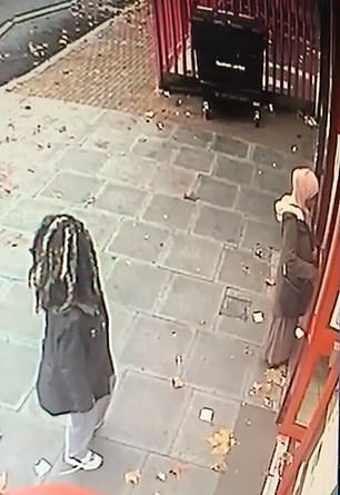 This is the shocking moment a woman (pictured wearing pink headscarf) is violently mugged by a female attacker (pictured wearing black with long hair) as she tries to get money from a cash point in Leytonstone, east London yesterday afternoon