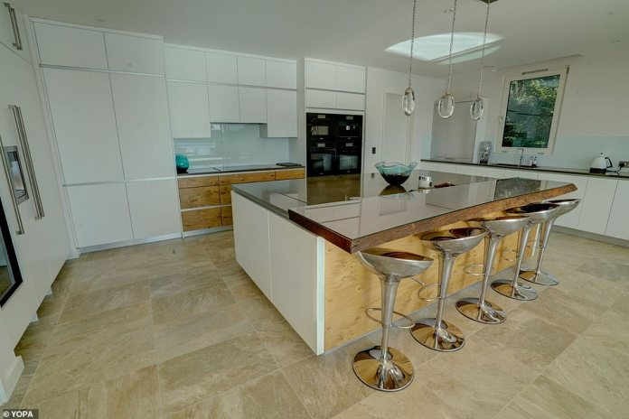 The modern kitchen includes white cabinets and a central island with seating, leaving plenty of room for parties