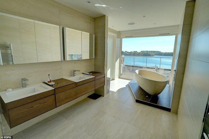 The oval bath tub has been perfectly placed to make the most of living at The Lakes by Yoo