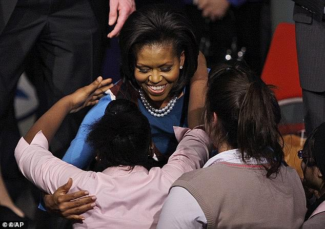 The First Lady, a graduate of Harvard Law School, pictured hugging students at Elizabeth Garrett Anderson Language College in 2009 is hoping to inspire another group of students with a visit to the Mulberry School in east London