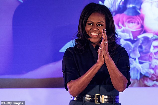 The former First Lady smiled and clapped her hands as she was welcomed onto a stage at the school