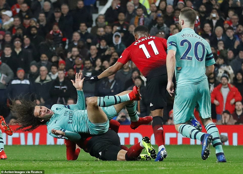 Matteo Guendouzi falls to the ground in pain following an extremely reckless foul from full-back Marcos Rojo (bottom)