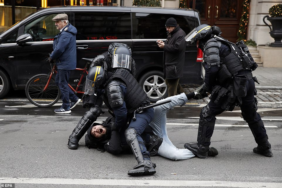 """French police arrest a man during a Yellow Vests demonstration. Macron, whose popularity is at a low ebb according to polls, has been forced into making the first major U-turn of his presidency by abandoning a fuel tax. Despite the climbdown, the """"yellow vests"""" continue to demand more concessions from the government, including lower taxes"""