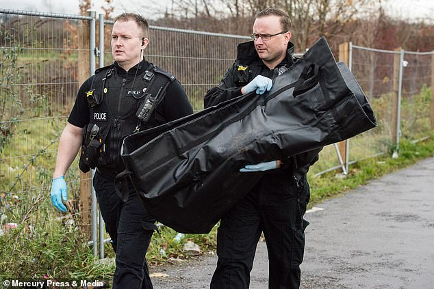 Officers were pictured carrying a body bag away from the scene after the human body part was recovered two years ago