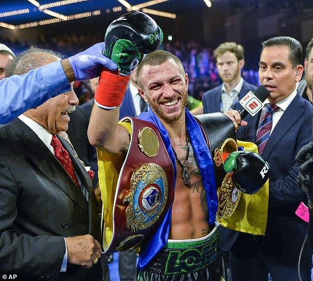 A delighted Vasiliy Lomachenko with the WBO and WBA lightweight belts after his unanimous points victory over Jose Pedraza in New York on Saturday night