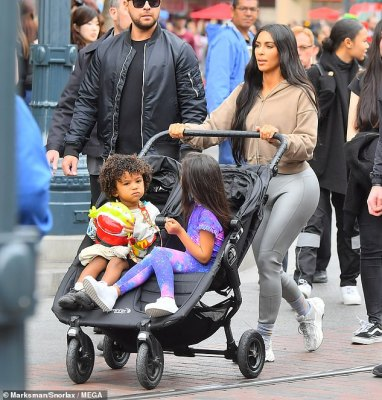 Kim at Disneyland:Kim, 38, was wearing a brown hoodie plus grey pants and white shoes, while pushing her kids in a dual stroller