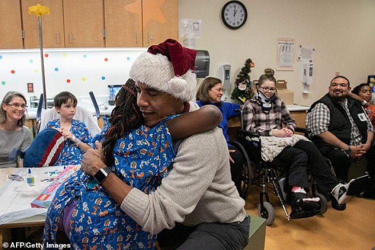Obama hugs a girl after presenting a Christmas gift to her in the hospital in DC