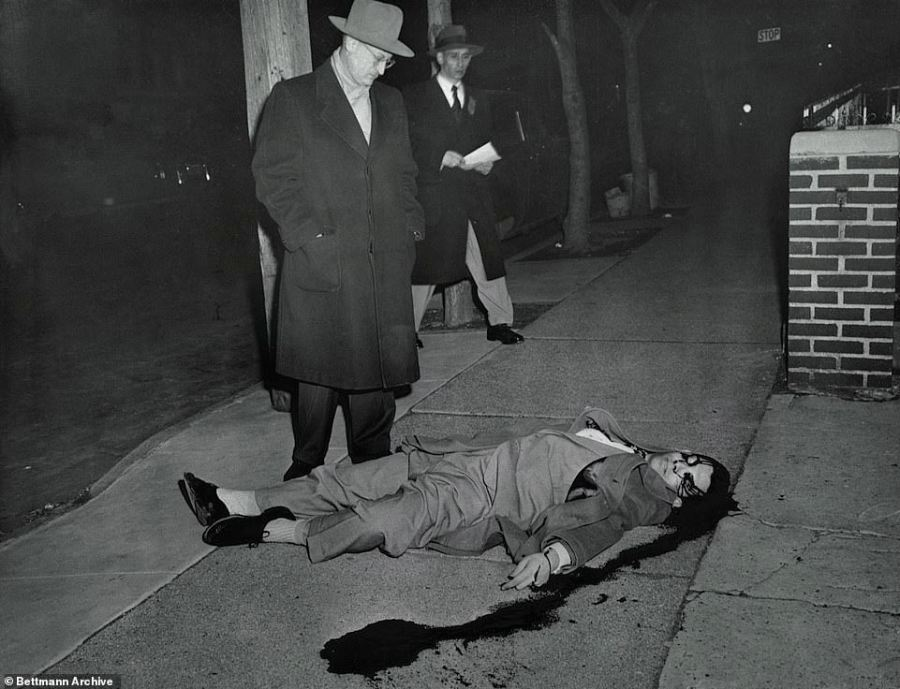 Death if a salesman: This 1952 photo shows the Assistant DA examining the body of Arnold Schuster, 24, - a Brooklyn pants salesman - who had tipped off police  on the whereabouts of American robber Willie Sutton after spotting him on a subway train following the criminal's daring jail escape