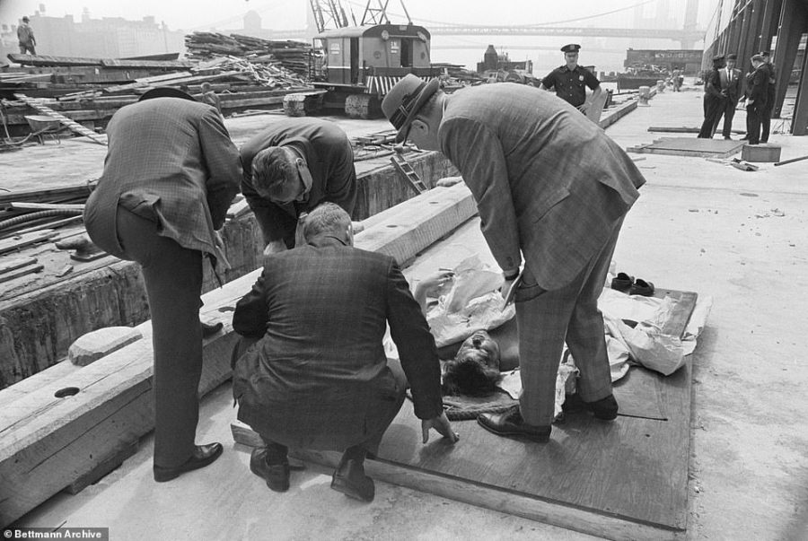 A medical examiner is pictured peering over the body of a man found floating in the East River in 1963. Bullet holes were found in the man's head