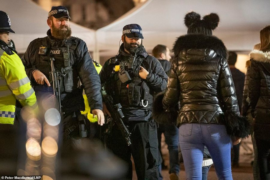 Armed police on The Mall watch as crowds go through a security check as they arrive to celebrate New Year's Eve in central London