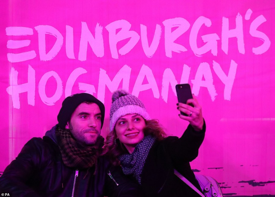 Theoni and Kypros Baker from Cyprus take a selfie on Princess Street  during the Hogmanay New Year celebrations in Edinburgh