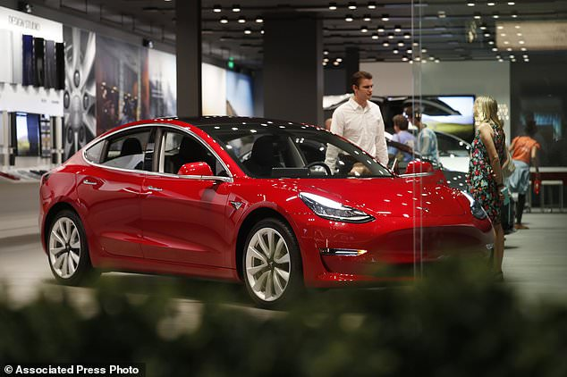 A prospective customer confer with sales associate as a Model 3 sits on display in a Tesla showroom in the Cherry Creek Mall in Denver.