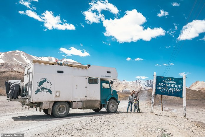 The Austrians Leander Nardin, his girlfriend Maria and their son Lennox, seven, pose next to their converted military truck, which is now their home. The family of three is currently traveling the world in the truck. They are depicted in the Central Asian country of Tajikistan
