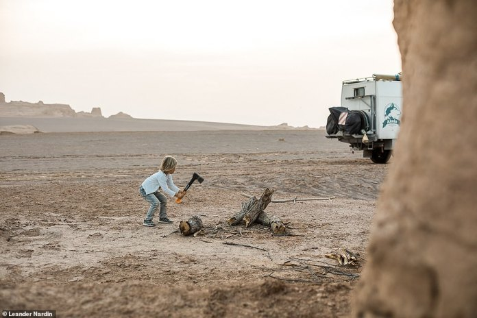 Lennox, a seven-year-old, uses an ax to split wood while traveling through the Lut desert in Iran. Lennox is at home but does not follow a standard school program