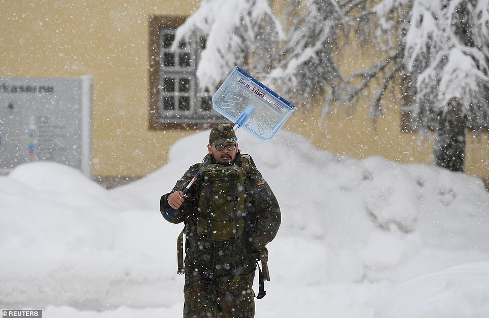 A soldier of the German armed forces Bundeswehr leaves the Jaeger barracks in Berchtesgaden to remove snow from buildings in Berchtesgaden