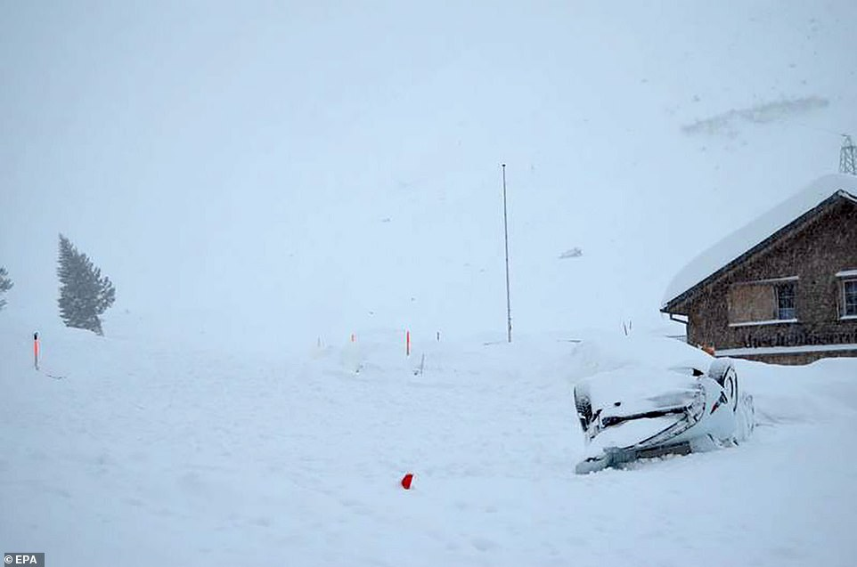 Eyewitnesses said at least one person had to be dug out of the snow when the avalanche struck the building. Pictures show how cars were left upturned in a car park outside
