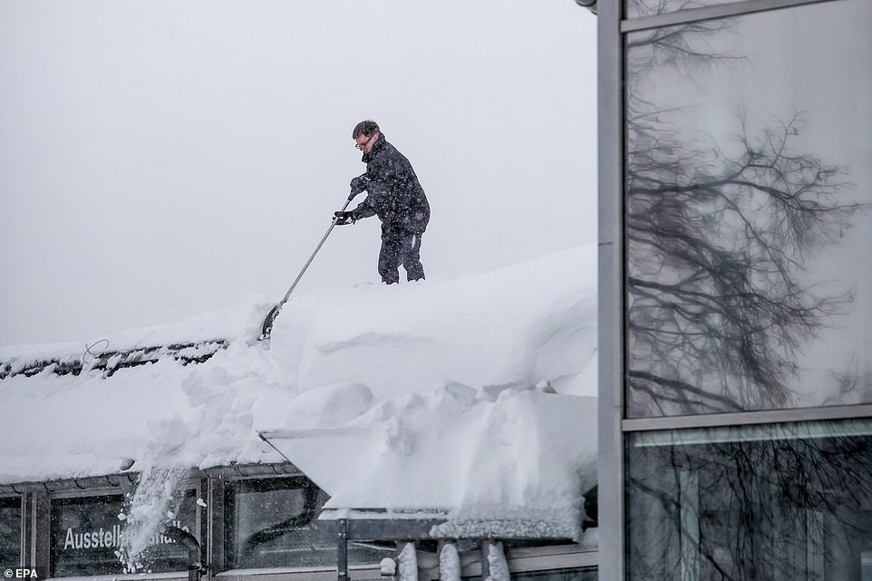 A man clears a roof of snow in Wolkenstein at Ore mountains, Germany, on Friday