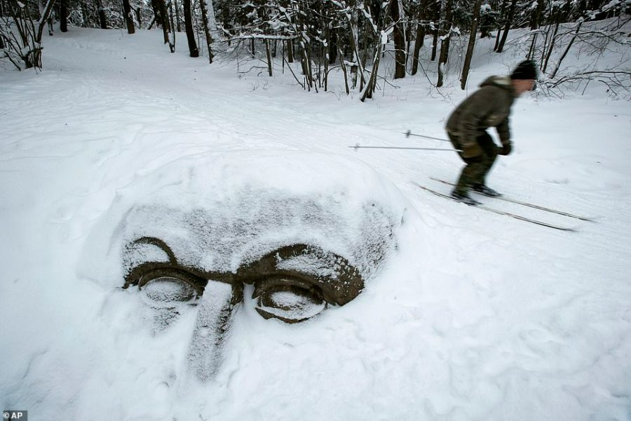 A man skis past a  head carved out of stone and buried in the snow in Sergievka park outside St.Petersburg, Russia