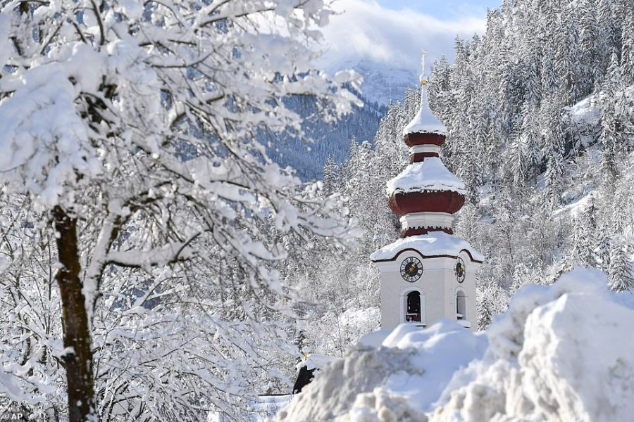 The steeple of the Loferer church is seen through the snow on Friday in the Austrian province of Salzburg