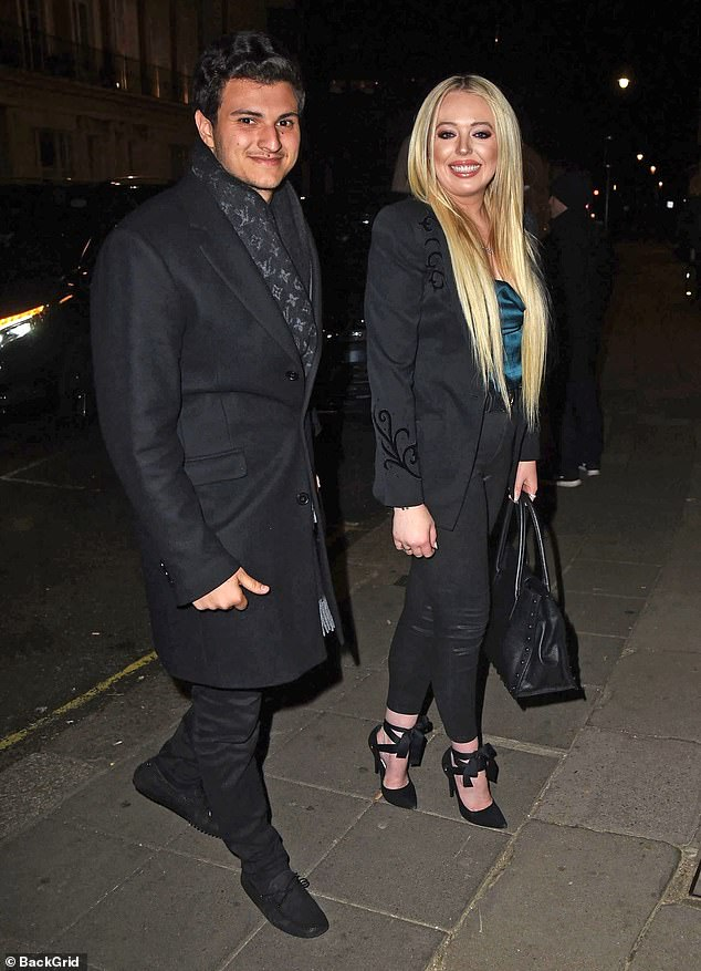 Cute couple: Michael, the heir of multibillion-dollar Nigerian conglomerate Boulos Enterprises, looked handsome in a black overcoat and matching trousers, paired with a designer scarf as he cosied up to his new love