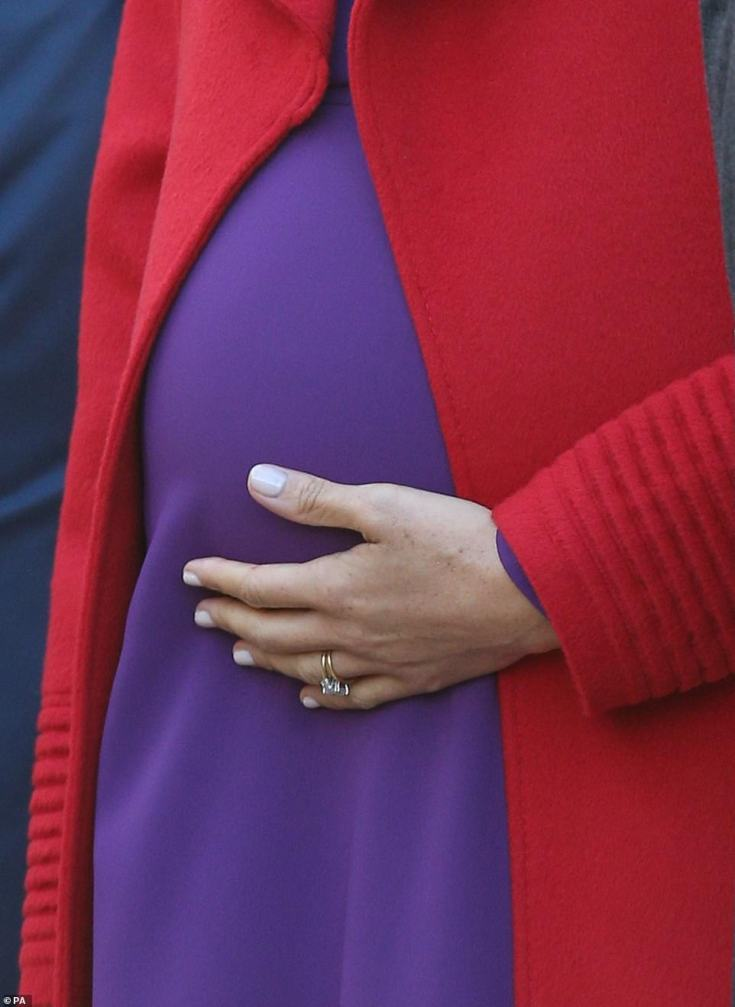 The Duchess is seen tenderly cradling her baby bump.Pregnant Meghan, who is expecting her first child with Harry this spring, is continuing to keep a busy schedule packed with royal engagements as she nears her due date