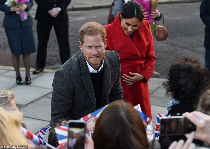 The couple lark around with the crowds in Merseyside this morning.Fans handed Meghan bouquets of flowers, while she looked particularly delighted with the gift of handmade paper flowers from a young fan from the Fun Train Day Nursery