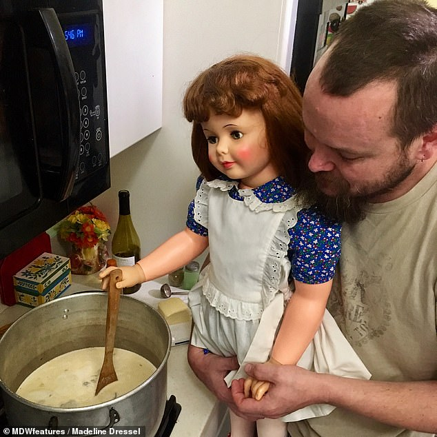Malachi and one of his plastic 'daughters' helping with the cooking. He and his wife Madeline set up their Instagram, all.my.plastic.children, last year as a parody account documenting their plastic family life