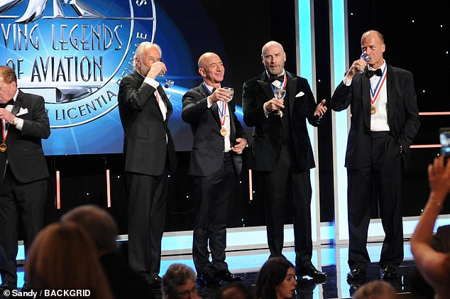 Bezos and Travolta enjoy a toast alongside other medal-adorned honorees Joe Clark (left) and Tom Enders (right)