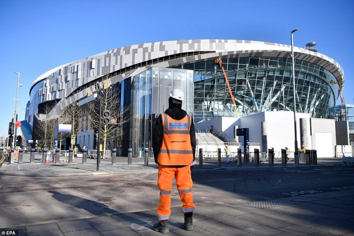 Another construction worker directs traffic outside the new Tottenham stadium on a sunny day north of London