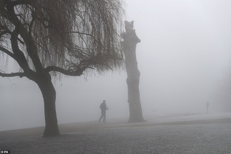 A man walks by the River Thames in Windsor this morning after the UK had its coldest night of the winter so far