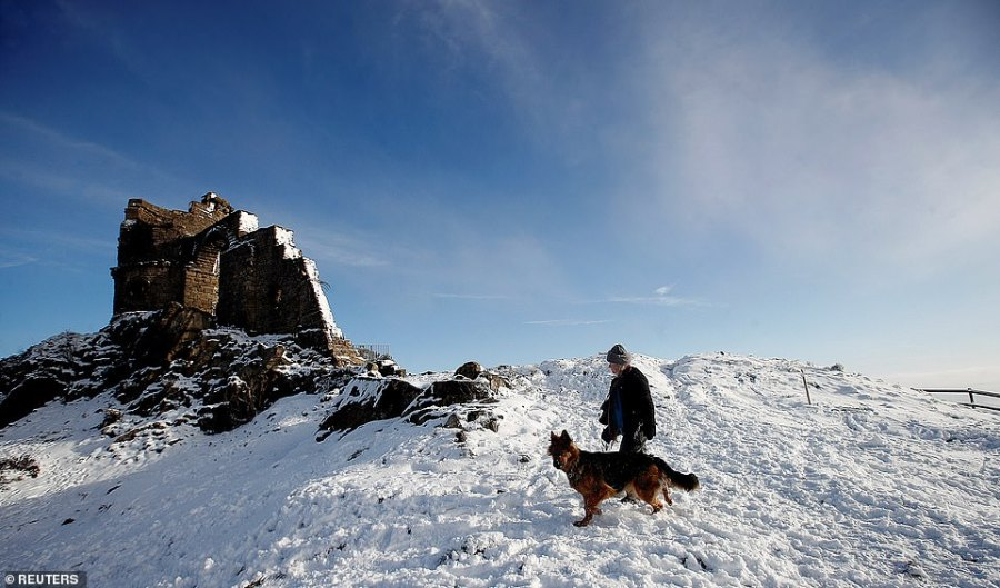 A dog walker in the snow walks past Mow Cop Castle in Odd Rode, Cheshire, today. The UK is expecting further