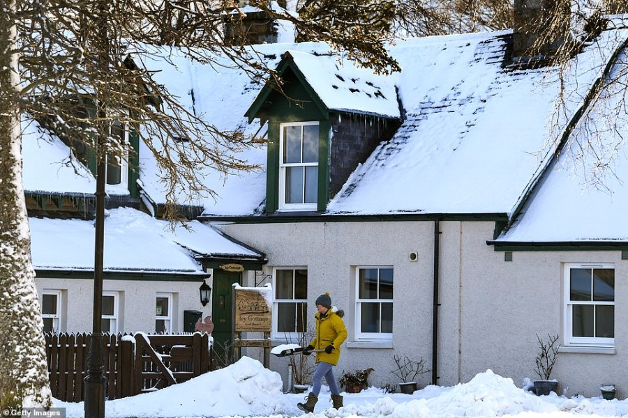 A woman walks along the snow with a shovel in Braemar, Aberdeenshire, which was the coldest place in Britain today