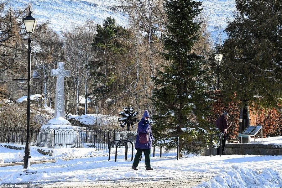 A woman walks on the snow today in Braemar, Aberdeenshire. It was the UK's coldest spot overnight where temperatures fell to -14.4C (6.1F) - well below the previous record for the 2018/19 winter of -10.8C (12.6F) set in the same village on January 18