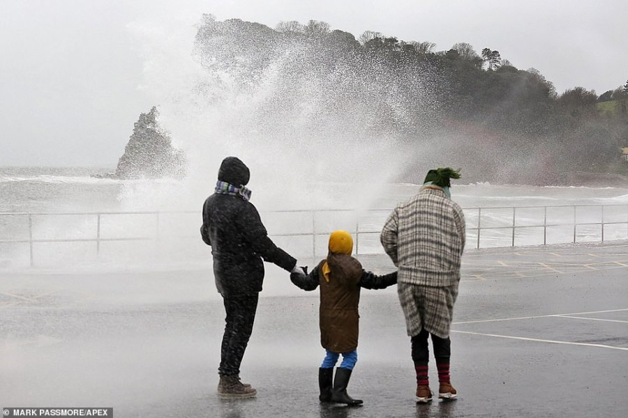 A family are soaked by huge waves crashing over the seafront at Teignmouth in Devon during stormy conditions today