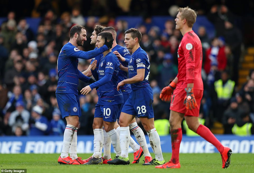 Chelsea players celebrate with the second goal scorer Hazard as Lossl reacts after getting beaten again