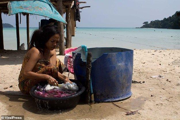 On voit une femme en train de laver des vêtements dans un village de Moken au bord de la mer d'Andaman en Thaïlande
